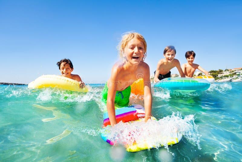 Lycklig pojke som rider vågorna med hans vänner arkivfoton