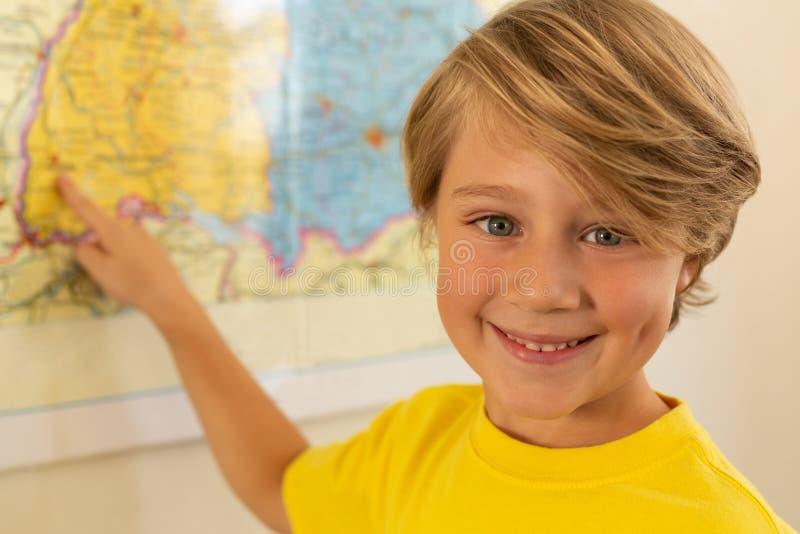 Lycklig pojke som ser kameran och pekar med hans finger på en översikt i klassrum royaltyfria bilder