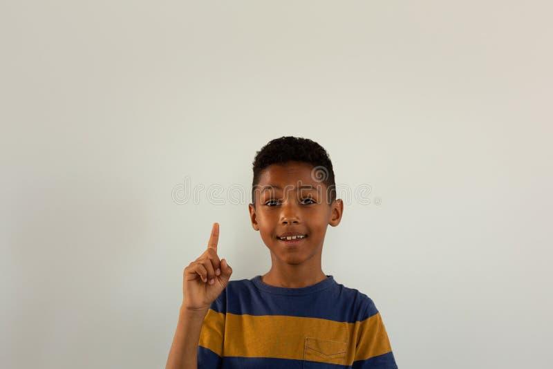 Lycklig pojke som ser kameran och pekar upp hans finger arkivfoto