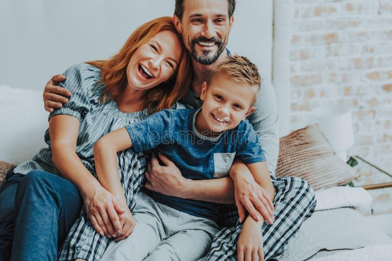 Lycklig pojke som sitter med föräldrar på säng royaltyfri foto