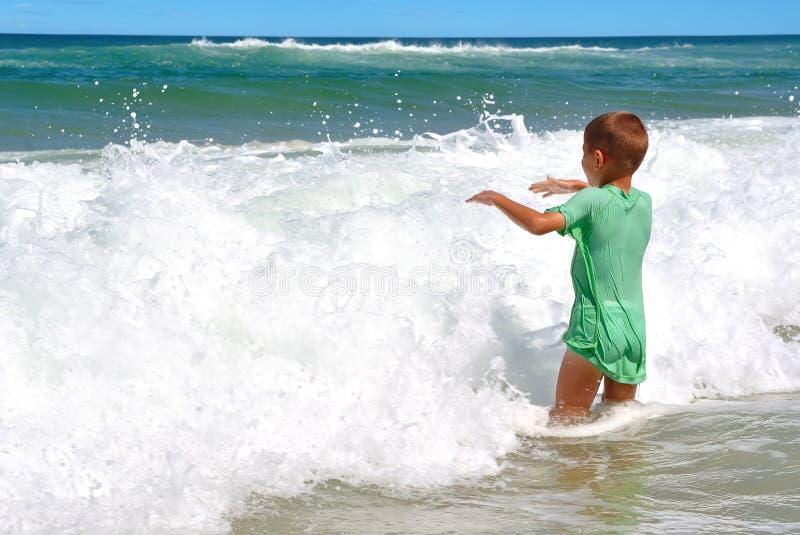 Lycklig pojke som spelar i vågorna arkivbilder
