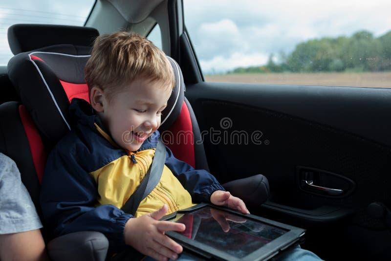 Lycklig pojke som spelar med touchpaden i bilen royaltyfria bilder