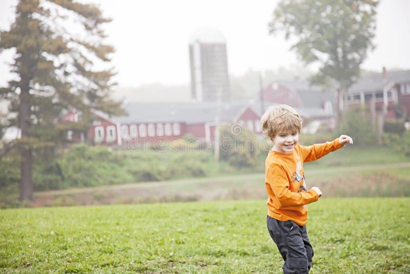 Lycklig pojke som spelar på lantgård arkivfoton