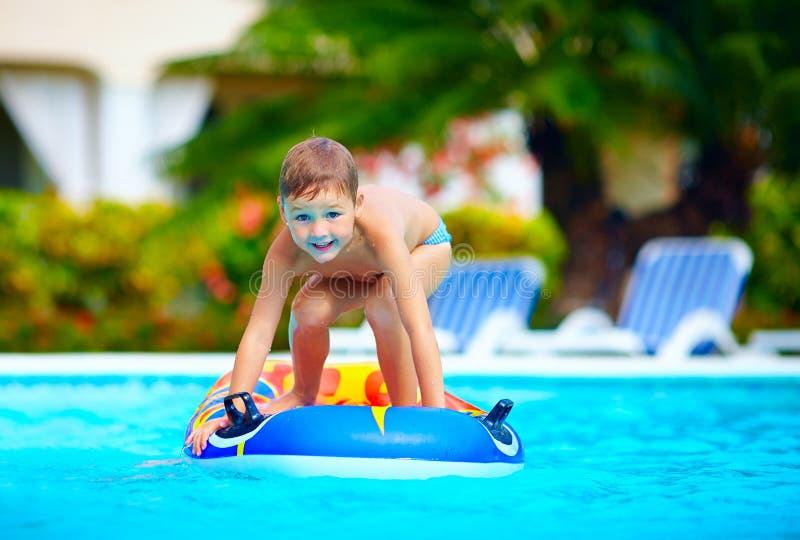 Lycklig pojke, unge som har gyckel i simbassäng fotografering för bildbyråer