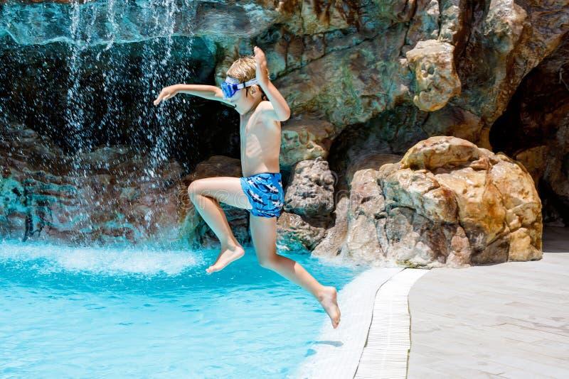 Lycklig pojkebanhoppning för liten unge i pölen och hagyckel på familjsemestrar i en hotellsemesterort Sunt barn som in spelar fotografering för bildbyråer