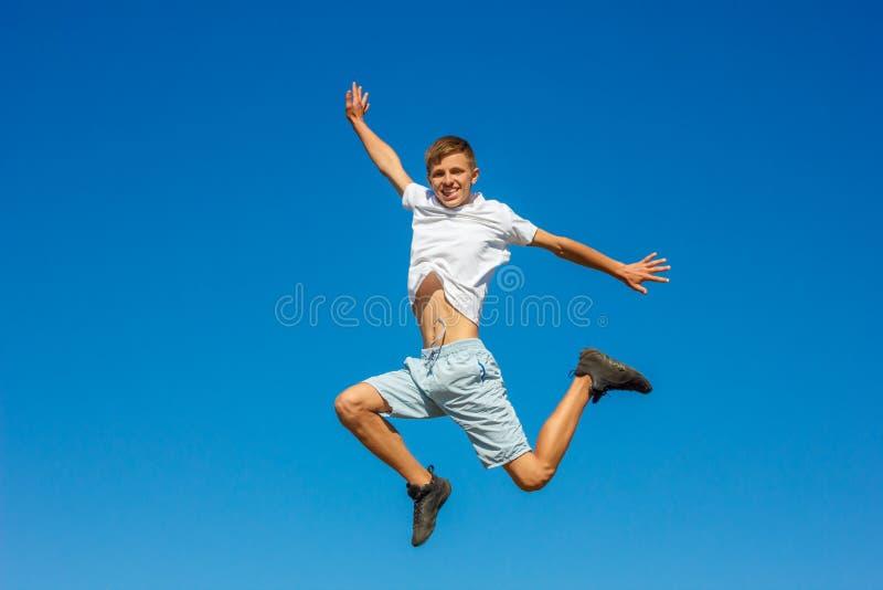 Lycklig pojkebanhoppning i den blåa himlen, begrepp av lycka royaltyfri bild