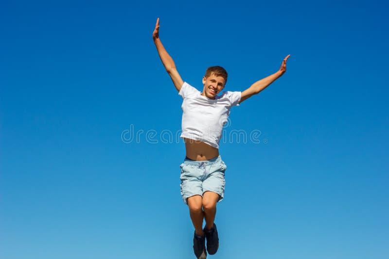 Lycklig pojkebanhoppning i den blåa himlen, begrepp av lycka royaltyfria foton