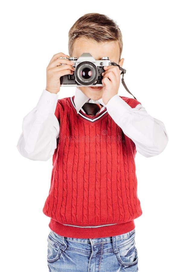 Lycklig pojkefotograf som rymmer en filmkamera isolerad på vit s arkivbild