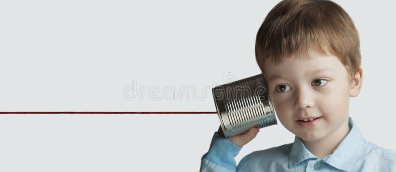 Lycklig pojkelek i telefonen för tenn- can royaltyfri foto