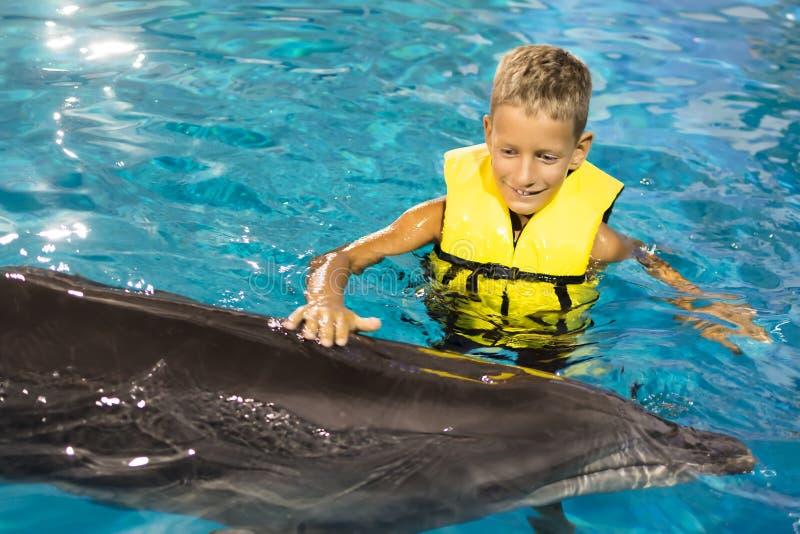 Lycklig pojkesimning med delfin i det blåa klara vattnet fotografering för bildbyråer