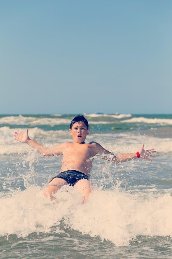 Lycklig pojkespring och banhoppning på grunt havsvatten royaltyfri fotografi