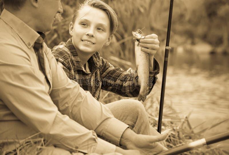 Lycklig pojketonåring och fader som tillsammans fiskar arkivbilder