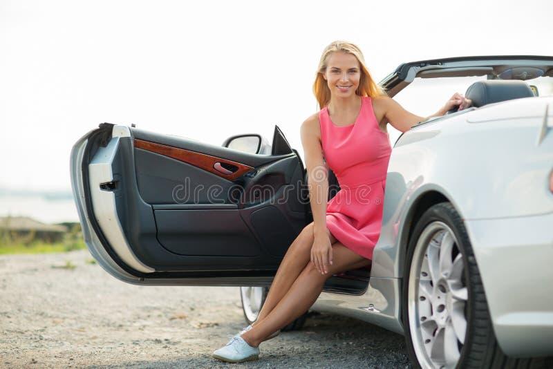Lycklig porisng för ung kvinna i konvertibel bil royaltyfri foto