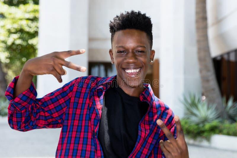 Lycklig posera ung vuxen man för afrikansk amerikan royaltyfri foto