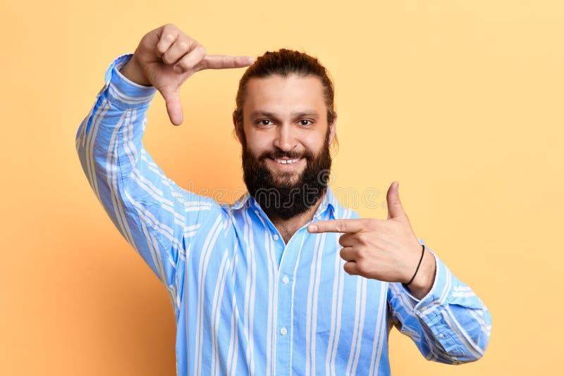 Lycklig positiv stilig ung man som gör ramen med fingrar royaltyfri foto