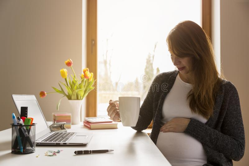 Lycklig preganant kvinna som ser hennes buk, medan arbeta ta ett avbrott från arbete Vara gravid på arbete royaltyfri fotografi