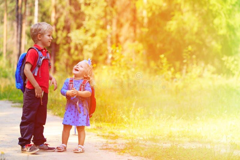 Lycklig pys och flicka med ryggsäckar i sommar arkivbild