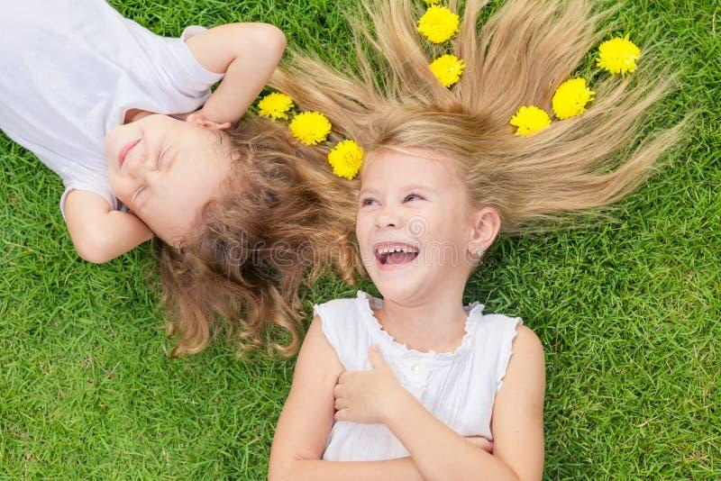 Lycklig pys och flicka som ligger på gräset royaltyfri fotografi