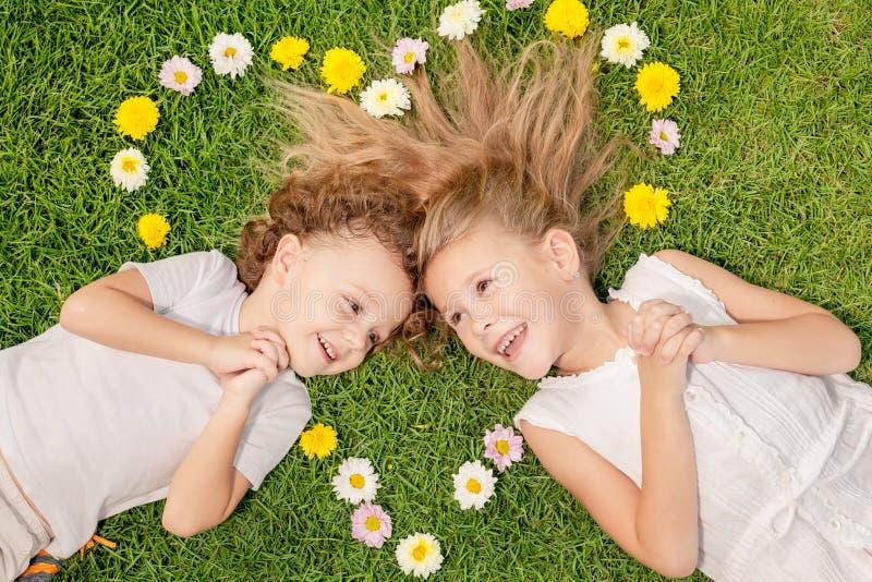 Lycklig pys och flicka som ligger på gräset royaltyfria bilder