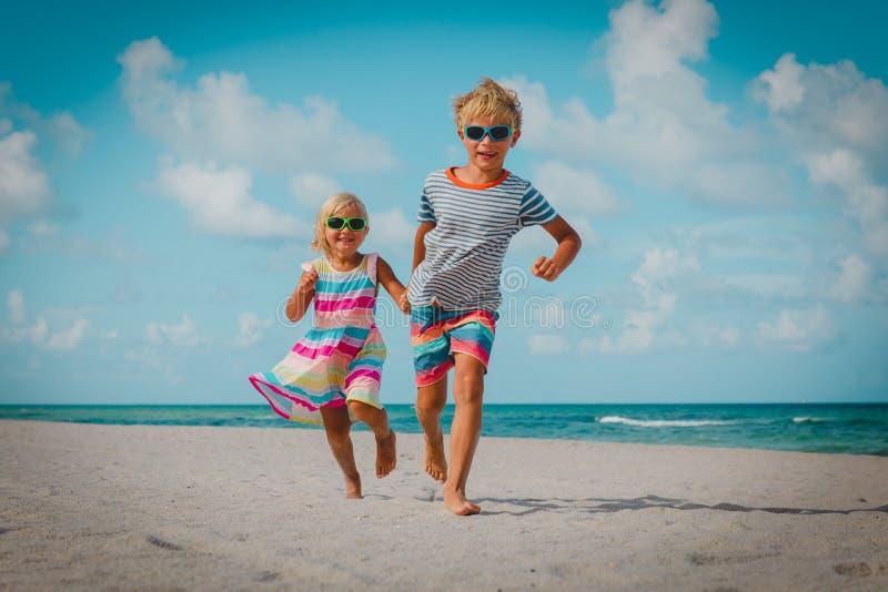 Lycklig pys- och flickakörningslek på stranden royaltyfri foto