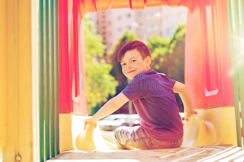 Lycklig pys på glidbana på barnlekplatsen royaltyfri foto