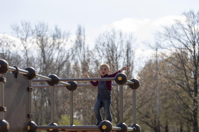Lycklig pys på ram för barnlekplatsklättring fotografering för bildbyråer