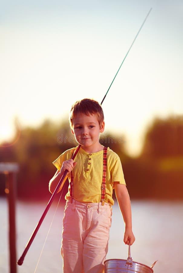 Lycklig pys som går efter lyckat fiske på dammet royaltyfria bilder