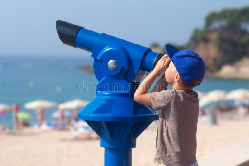 Lycklig pys som ser i teleskop på den Lloret stranden arkivfoton