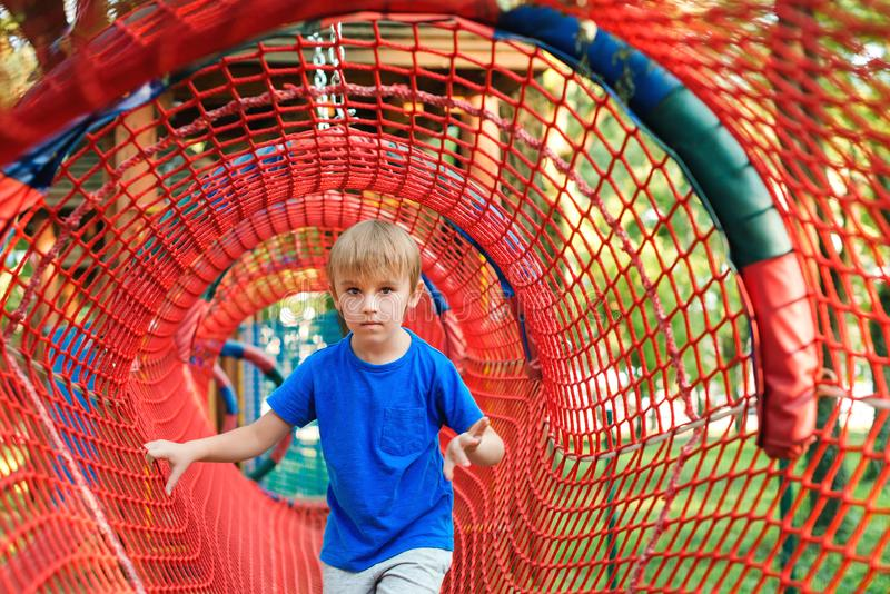 Lycklig pys som spelar i reptunnel på den moderna lekplatsen lycklig din feriesommar f?r familj Lycklig och sund barndom arkivbilder