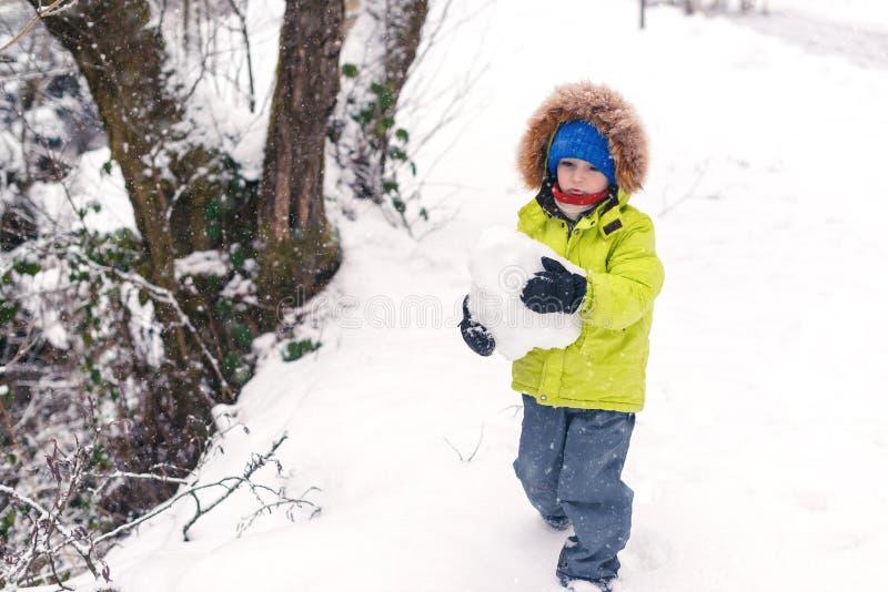 Lycklig pys som spelar i snö Litet barn som har gyckel på vinterdag vinter för snow för pojkeferielay Roligt bära för pojke som ä arkivbild