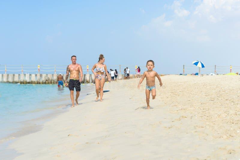 Lycklig pysspring på den tropiska stranden för sand Positiva mänskliga sinnesrörelser, känslor, glädje E arkivbild