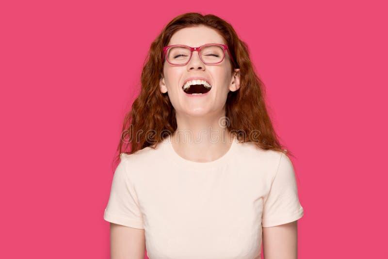 Lycklig rödhårig flicka i exponeringsglas som skrattar på skämtet arkivbilder