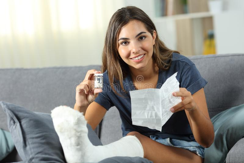 Lycklig rörelsehindrad kvinna som visar en flaska av preventivpillerar arkivbild