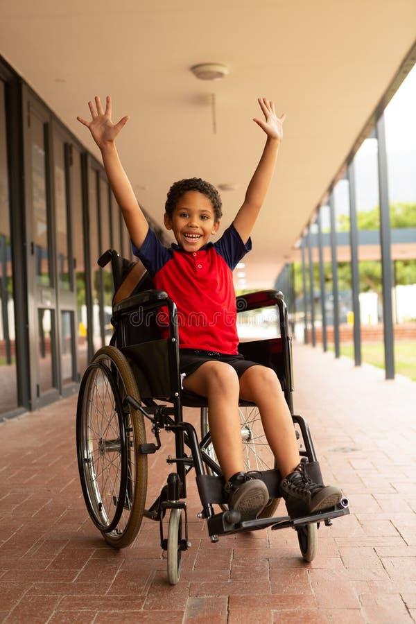 Lycklig rörelsehindrad skolpojke med armar upp att se kameran i korridor royaltyfri fotografi