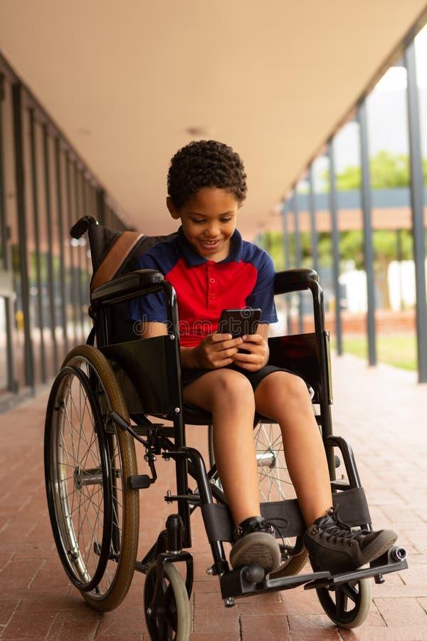 Lycklig rörelsehindrad skolpojke som använder mobiltelefonen i korridor arkivfoto