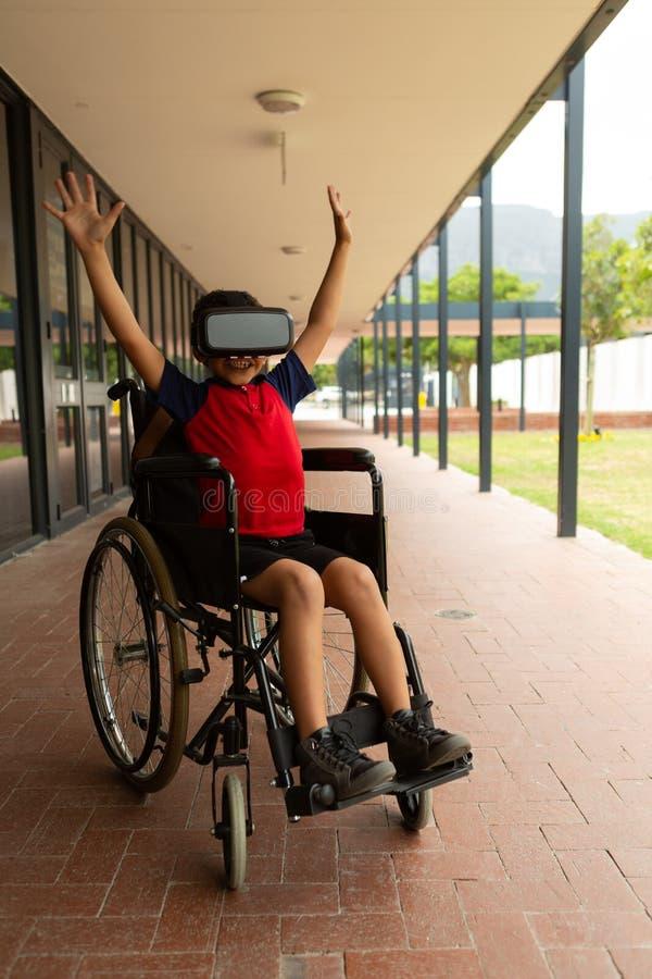 Lycklig rörelsehindrad skolpojke som använder virtuell verklighethörlurar med mikrofon i korridor royaltyfria bilder