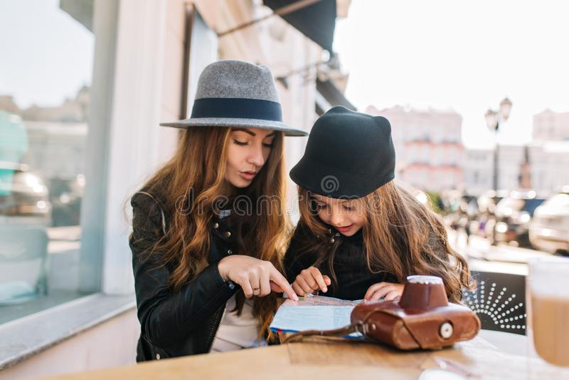 Lycklig resande familj Ung moder med dottern som sitter i kafét på den soliga stadsbakgrunden, blick på översikten mom arkivbilder