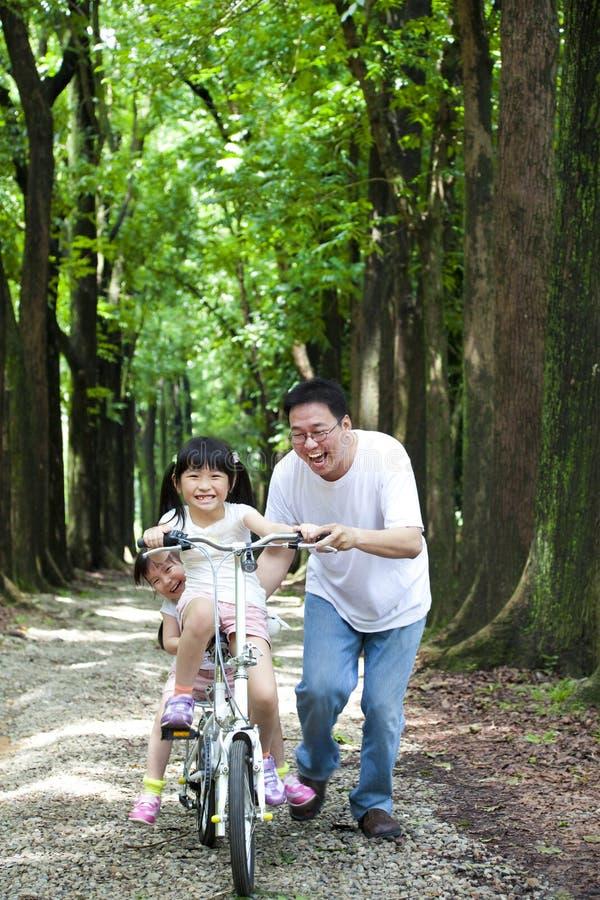 lycklig ridning för asiatisk cykelfamilj royaltyfri bild