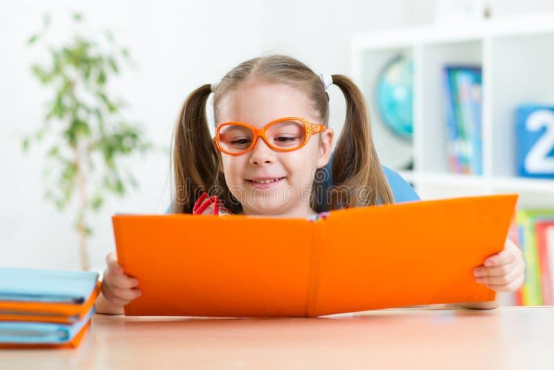 Lycklig rolig barnflicka i exponeringsglas som läser en bok royaltyfria bilder
