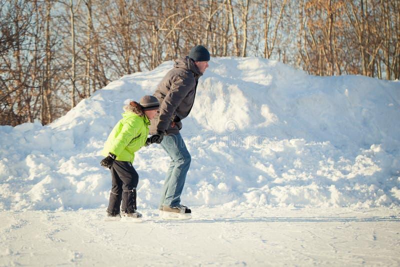 Lycklig rolig fader och son som lär att åka skridskor arkivfoton