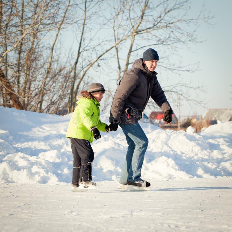 Lycklig rolig fader och son som lär att åka skridskor fotografering för bildbyråer