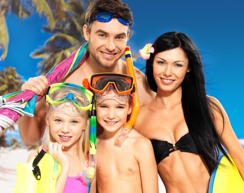 Lycklig rolig familj med två barn på den tropiska stranden arkivfoton