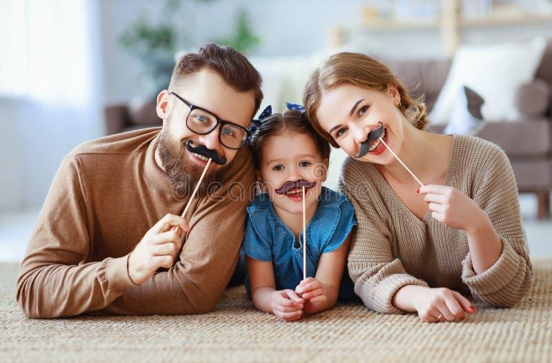 Lycklig rolig familjmoderfader och barndotter med mustaschen på pinnen arkivbilder