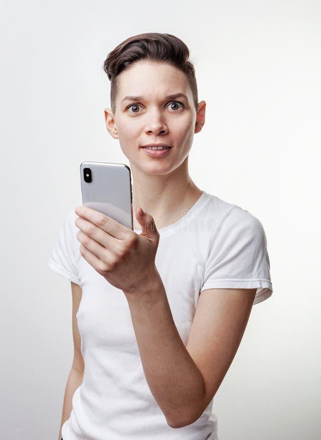 Lycklig rolig millennial kvinnas fira seger eller seger, triumf som rymmer en telefon Gladlynt upphetsad flicka och att skratta o arkivbilder