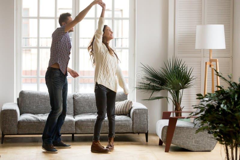 Lycklig romantisk pardans i vardagsrum hemma tillsammans royaltyfria bilder