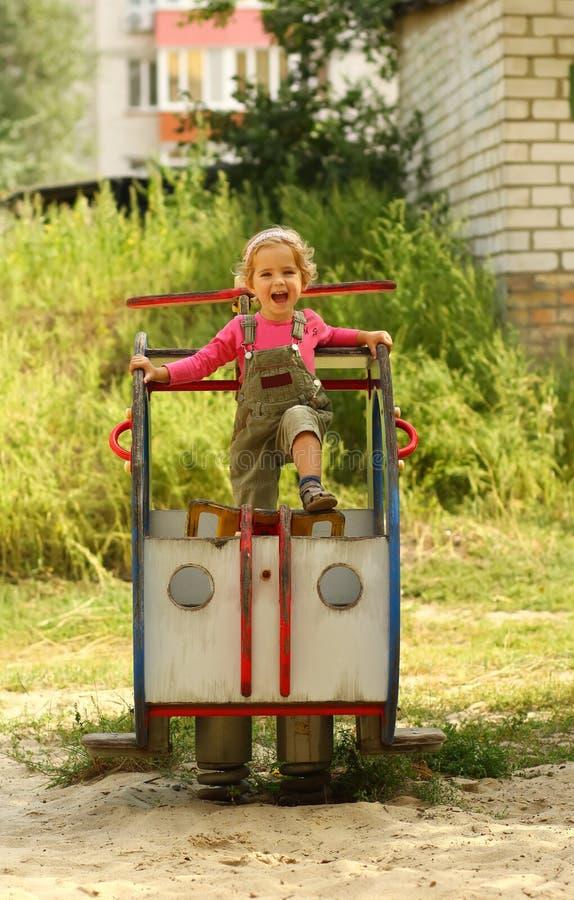Lycklig ropa emotionell litet barnflickapilot som poserar på lekplatshelikoptern royaltyfri foto