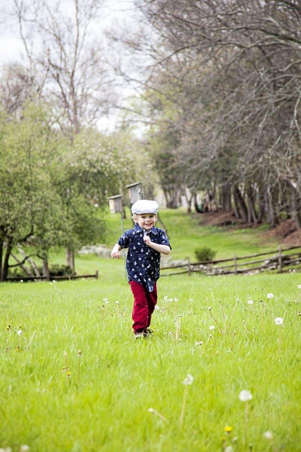 lycklig running för pojke arkivfoto