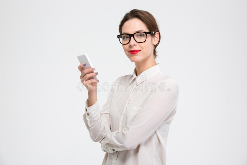 Lycklig säker ung affärskvinna i exponeringsglas genom att använda smartphonen