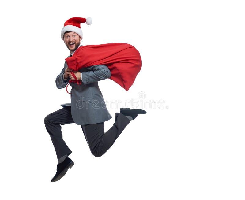Lycklig Santa Claus banhoppning med påsen av gåvor och gåvor royaltyfria foton
