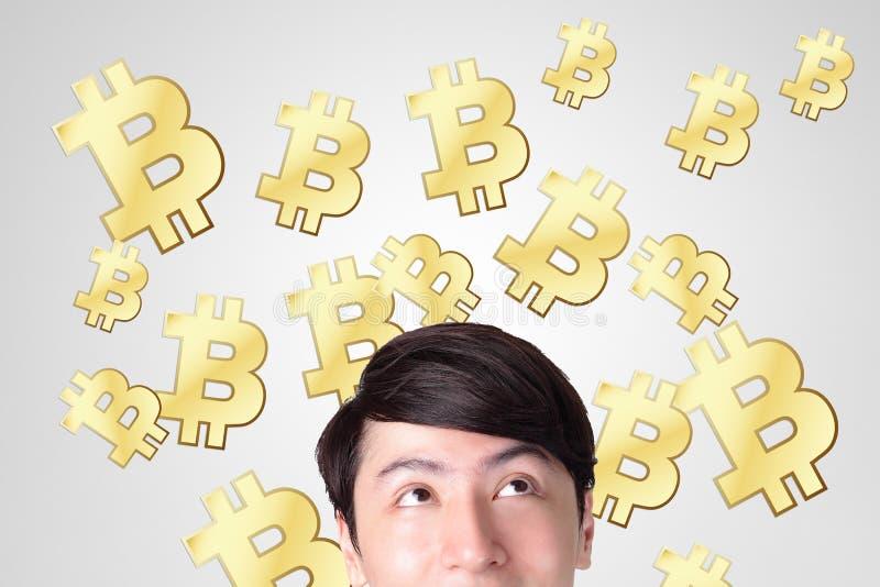 Lycklig seende bitcoin för ung man fotografering för bildbyråer